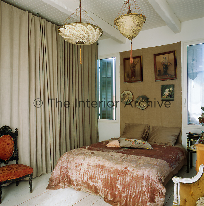 The bedroom is decorated in soft, calming colours with neutral curtains and a taupe linen hanging as a headboard feature. The bed is draped with an antique velvet bedspread.