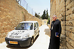 A Benedictine monk stands a church car vandalized with graffiti and with its tires slashes next to the Dormition Abbey (R) just outside Jerusalem's Old City walls, 31 May 2013. Anti-Christian graffiti was spray painted on two cars and near doors to the well-know and popular pilgrim site sometime overnight with slogans reading, 'Christians are monkeys', 'Christians are slaves,' and 'Havat Maon,' in reference to a Jewish settler outpost in the West Bank. Police are investigating. The Abbey, according to tradition, is the site where the Virgin Mary died, and is close to the site of Jesus' Last Supper. Photo by Saeed Qaq