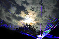 A double exposure of rave lights and the cloudy moonlit sky.