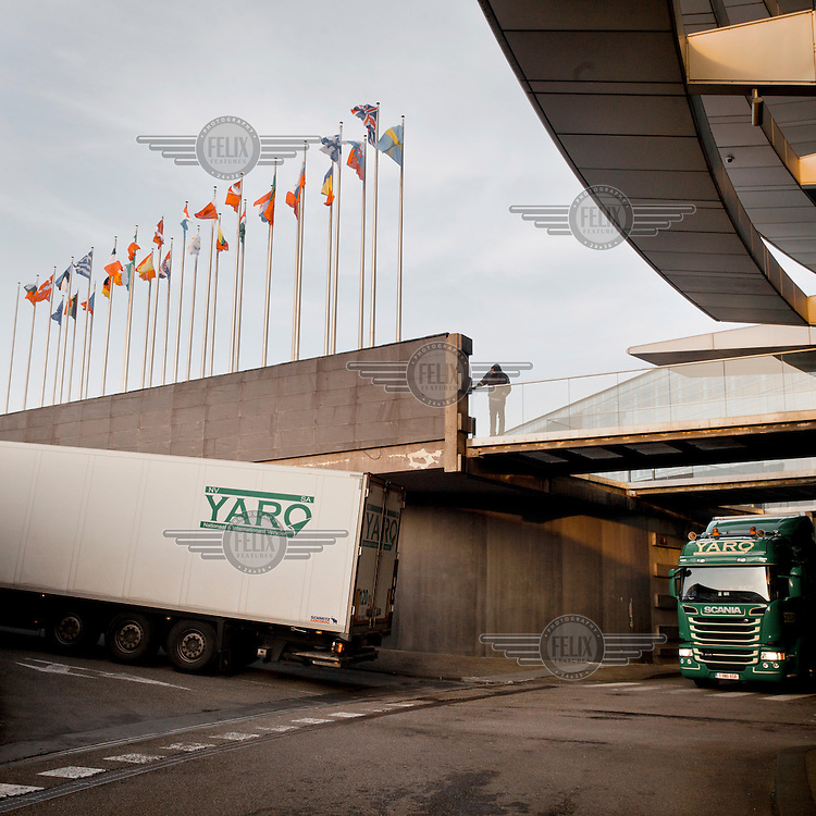 A security guard watches as lorries leave a below-ground service area, at the European parliament building in Strasbourg, loaded with document containers called 'cantines' for transportation to Brussels following the conclusion of the plenary session in Strasbourg. Every month thousands of parliament's employees travel back and forth between the three sites of European government in Brussels, Strasbourg and Luxembourg, with their documents following them.