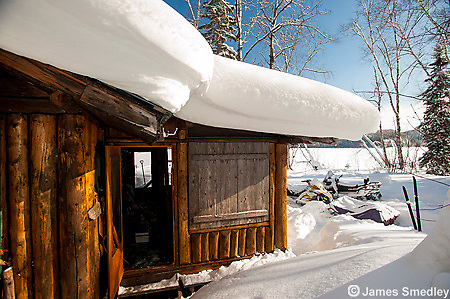 Remote snow covered cabin by a frozen lake in winter.