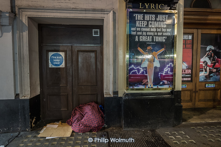 Rough sleeper's possessions and sleeping place in the doorway of the Lyric Theatre, Shaftesbury Avenue, London.