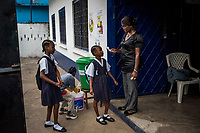 """MONROVIA, LIBERIA - FEBRUARY 17: Vice principal, Venoria Crayton, takes the temperature of incoming school students as they enter the school grounds, on the second day of school, since schools closed due to the Ebola outbreak 6 months ago, at the C.D.B. King Elementary School on February 17, 2015 in Monrovia, Liberia. Ebola destroyed and devastated our land,'' Venoria Crayton, the vice principal, told her pupils. """"It brought us sadness, it brought us pain. Some of your neighbors died, right? Some of your neighbor's children died, right? But you are here."""" Though Ebola cases have receded into the single digits in Liberia, lingering fear and a depressed economy have dampened the turnout at schools. Many have yet to reopen, having failed to meet the minimum requirements put in place to prevent the transmission of the virus. Many of those that have reopened – like C.D.B. King, which, though located in the center of the capital, lacks electricity and running water, and has only a few toilet stalls for a student population that numbered 1,000 before Ebola — are struggling.<br /> Daniel Berehulak for The New York Times"""