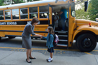 Dr. Donna Hargens greets students as they exit a bus.