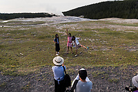 Tourists dance and pose for pictures on land between the boardwalk and Old Faithful after it erupted in Yellowstone National Park, Wyoming, USA. Federal law prohibits walking on this section of land due to the instability of ground near geysers and the danger of hot water directly beneath the surface. In June 2016, a Chinese national was fined $1000 by the National Park Service for walking off the boardwalk in the thermal area in the Mammoth Hot Springs area in the north of Yellowstone.