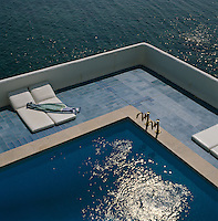 An aerial view of this corner of a swimming pool terrace with the calm waters of the Mediterranean below