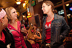 Kategory 5, in the jean jacket, talks with Glitterotica, to her right, and Hot T'Wally at Barton Springs Saloon after a bout between the Hellcats and Pdutas del Fuego in Austin, Texas.