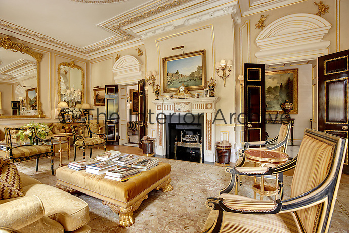 An opulent drawing room with an ornate gilded ceiling, a black fireplace and furnished with antique furniture. Two sets of double doors open onto ante-rooms.