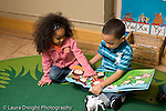 Education preschoool children ages 3-5 boy and girl sitting together looking at picture book girl touching illustration in book horizontal