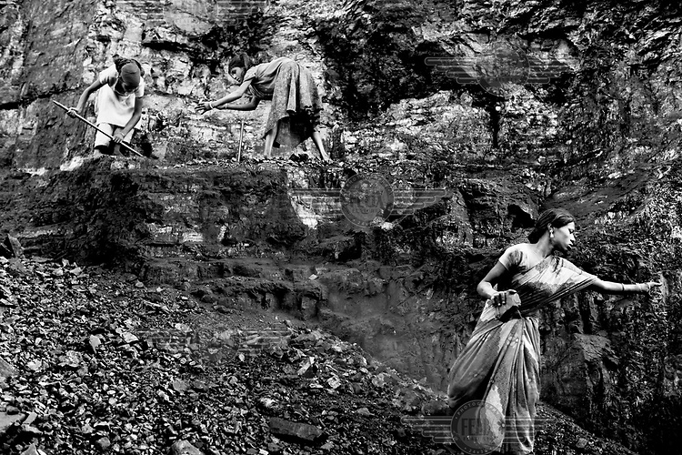 Women scavenge coal from an open cast mine. On the margins of such mines small communities of people make a precarious living scavenging coal and selling charcoal and coke they make from it. Below ground permanent fires burn, fuelled by seams of coal. The ground can be too hot to walk on and there is an ever present danger that houses will collapse into the vast underground caverns that are left unfilled after mining operations have ended.