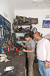 HURGHADA - EGYPT - 03 March 2015 -- Taha leaning to repair motorcycle part in mechanical workshop, owner Hamada watching him. -- Photo: Kimmo HAGMAN / EUP-IMAGES