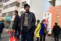 Uighurs and Hans wait for buses outside a Han shopping mall outside the Old City section of Kashgar, Xinjiang, China.