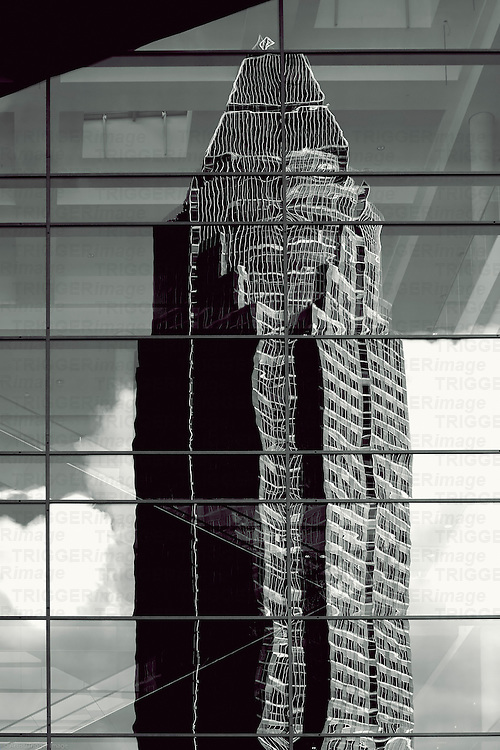 The abstract photograph of the reflection of the fair tower in Frankfurt in a glass facade.