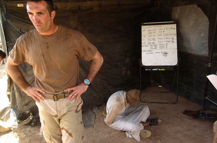 A U.S. commander takes a break from questioning a suspected insurgent at the combat outpost of Rawah, near the Syrian border. Tuesday July 19, 2005