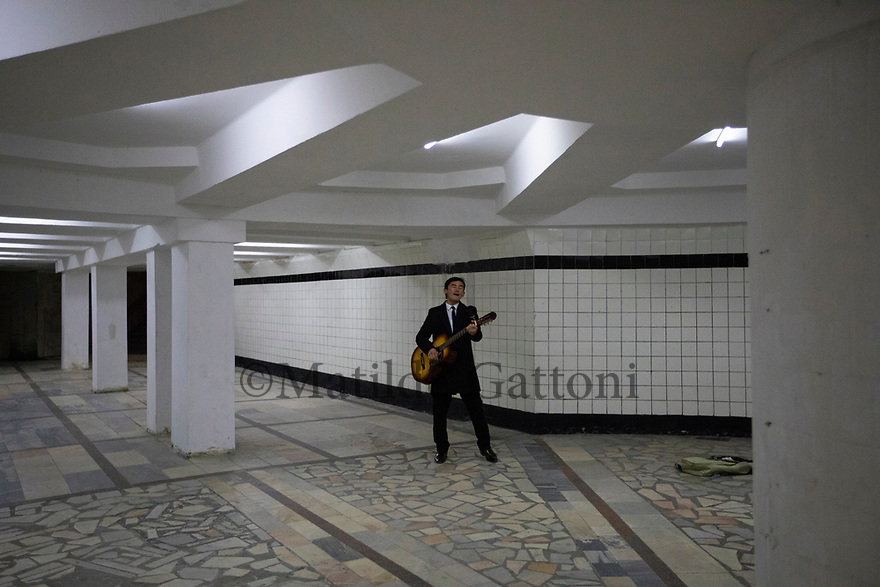 Uzbekistan - Tashkent - A musician playing the guitar and singing in an underground passage at night.