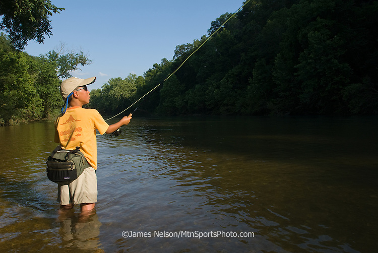 A nine-year-old boy casts a fly for bluegill on the James River, Missouri.