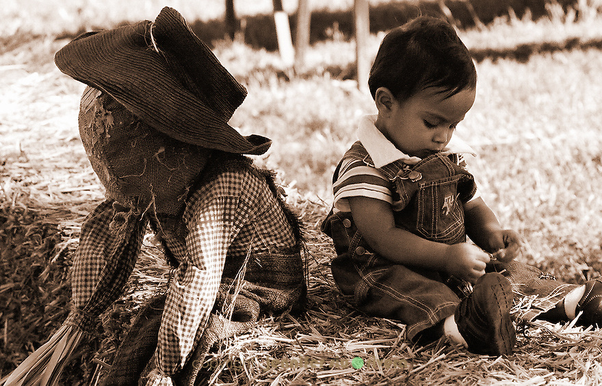 Model - Lael Akan Rivera, 1 year old. Pumpkin Patch at Medina, Texas. baby sitting back to back with a scarecrow buddy.