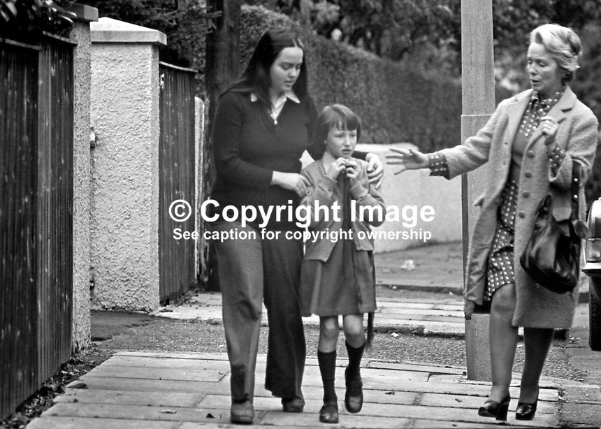 Deirdre Conaghan, the nine year old daughter of Roman Catholic Judge Rory Conaghan, and a witnesss to her father's murder at Beechlands, Belfast, N Ireland, is hustled away by neighbours. On the same day at a approximately the same time a Protestant magistrate, Martin McBirney, was also murdered. A subsequent Provisional IRA statement said they had been assassinated for &quot;collaborating with the British war machine&quot;. 197409160494a<br />