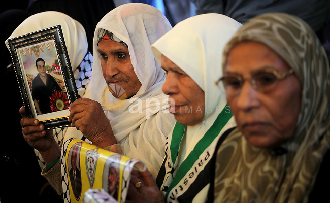 Palestinian women hold pictures of their prisoned relatives in Israeli jails as they gather in a weekly activity calling for their liberty at the Red Cross headquarters in Gaza City on December 03, 2012. Photo by Ashraf Amra