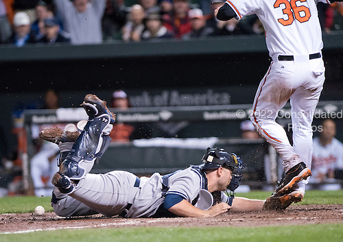 New York Yankees catcher Brian McCann (34) lunges to tag Baltimore Orioles catcher Caleb Joseph (36) as he scores his team's final run in the seventh inning at Oriole Park at Camden Yards in Baltimore, MD on Tuesday, April 14, 2015. The Orioles won the game 4 - 3.<br /> Credit: Ron Sachs / CNP<br /> (RESTRICTION: NO New York or New Jersey Newspapers or newspapers within a 75 mile radius of New York City)