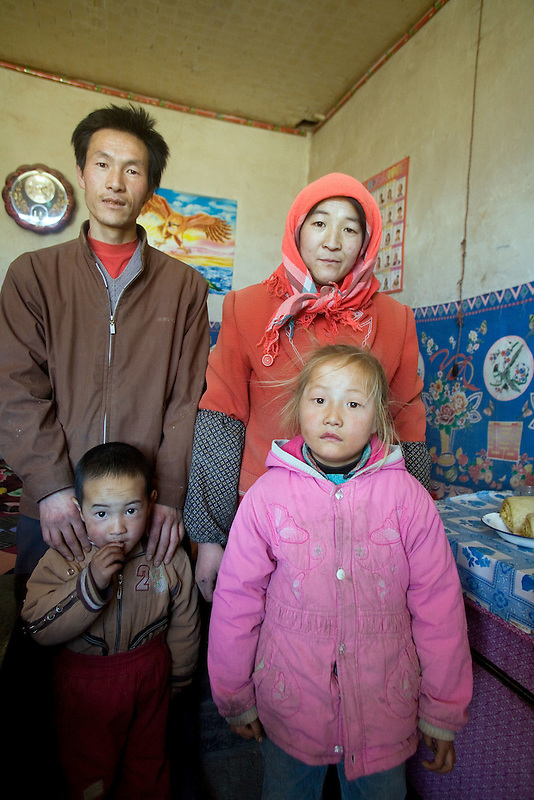 Blonde six year old Gu Maina, with her family, parents and brother in their modest home near Liqian Village.