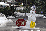 A snowman with a stop sign blocks a side street with a down tree across it in Ellington Conn., Monday, Oct. 31, 2011, as some residents stand in the street taking a break from the clean up. The unseasonably early nor'easter had utility companies struggling to restore electricity to more than 3 million homes and businesses. (AP Photo/Journal Inquirer, Jim Michaudl)