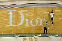 Men put the finishing touches to an elaborate marketing campaign for fashion designer, christian dior in Shenzhen, China..