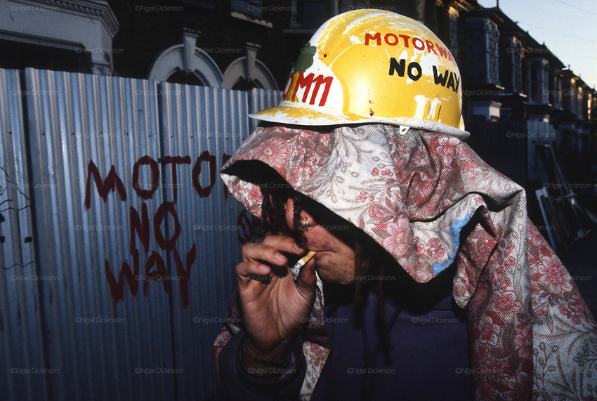 Protester smoking a cigarette at night with 'No Motorway' graffiti. Near to Road protestor squats indoors. Along the M11 route. Cambridge Park Wanstead, Leytonstone, London. <br />