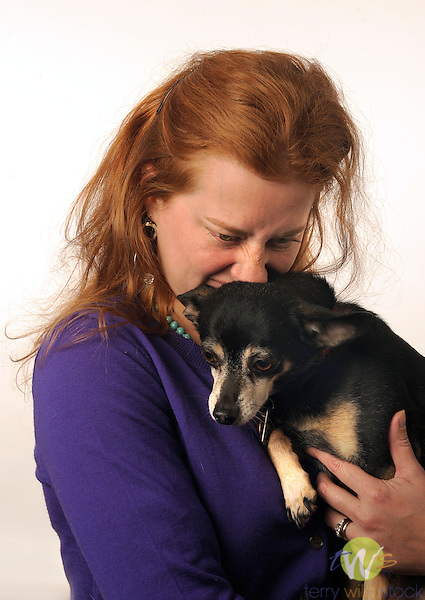 Woman with red hair holding dog.