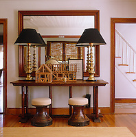 In the entrance hall an architectural model of a barn and a pair of English brass lamps sit on an American harvest table