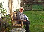 A292YD Elderly lady sitting on garden bench in front of white cottage
