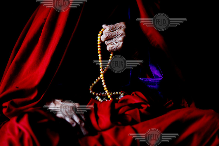 A monk prays with prayer beads at the Taktsang (Dzong) Monastery high up in the Paro Valley.