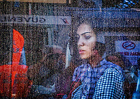 Fine Art Print Photograph. Urban Street Photography Istanbul, Turkey.<br /> The expression of this girl deep in thought as we peer through the window of the tram to see her expression. The deep saturated colours and rain droplets on the glass create the somber mood of this print.