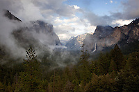 Storm clouds break open to blue skies following a rain storm in Yosemite Valley, California. El Capitan and Bridal Veil Falls can be seen in the distance.