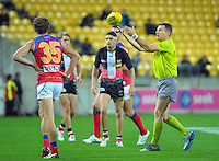 The umpire throws the ball up for a restart during the Australian Rules Football ANZAC Day match between St Kilda Saints and Brisbane Lions at Westpac Stadium, Wellington, New Zealand on Friday, 25 April 2014. Photo: Dave Lintott / lintottphoto.co.nz