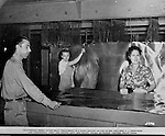 Spokane Washington and McCook Illinois: View of Swindell-Dressler brochure highlighting the Electric Furnaces designed, constructed and installed in two Alcoa plants during World War II. The caption reads: Flattening sheet after heat treatment is a group affair as far as Mr. and Mrs. C.J. Ferguson are concerned. They are shown left and right and Palma Severson, center, helps them.