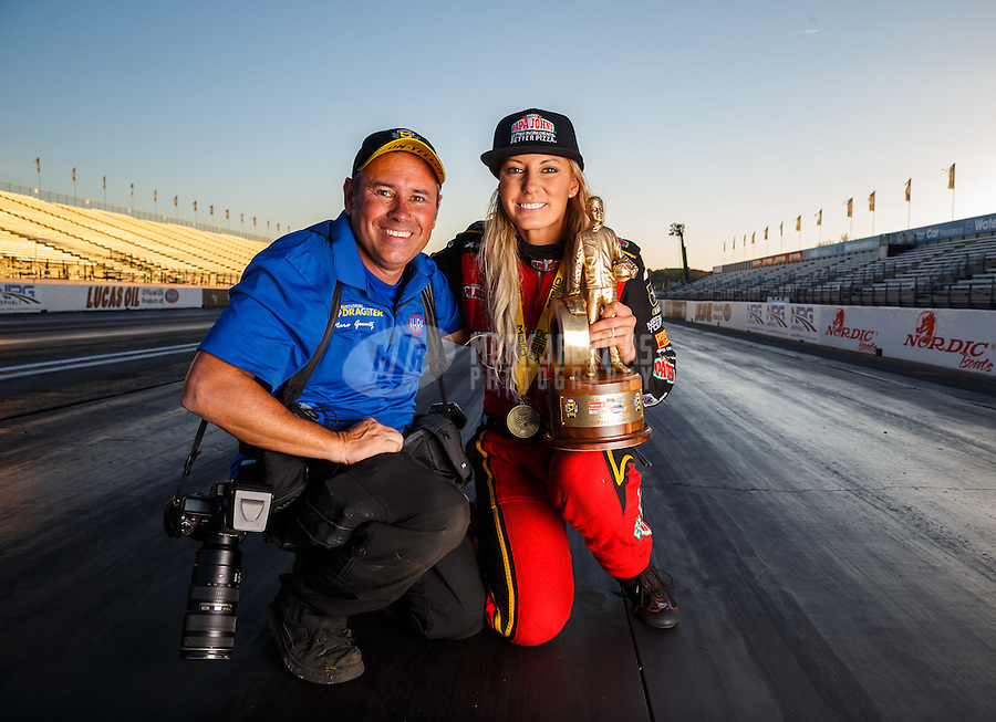 Feb 12, 2017; Pomona, CA, USA; NHRA top fuel driver Leah Pritchett poses for a portrait with photographer Marc Gewertz as she celebrates after winning the Winternationals at Auto Club Raceway at Pomona. Mandatory Credit: Mark J. Rebilas-USA TODAY Sports