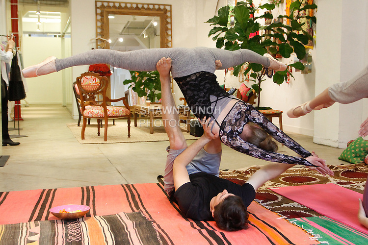 Yogi lifts ballerina to execute an acro yoga position; while the ballerina is dressed in balletwear, during the Free People FP Movement collection launch at 218 West 40 Street New York City on May 1, 2014.
