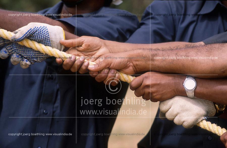 INDIA Tamil Nadu, Muppandal, worker hold rope, construction of steel tower for Vestas wind turbine, Vestas RBB is a danish indian Joint Venture / INDIEN Tamil Nadu Muppandal, Aufbau von Gittermasten fuer Windkraftanlagen der Firma Vestas RBB , ein daenisch indisches Joint Venture, Windpark am Kap Comorin, Arbeiter halen ein Seil