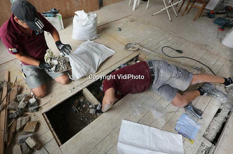 Foto: VidiPhoto<br /> <br /> ARNHEM - Personeel van Hegeman Bouwpartners uit Arnhem verwijdert woensdag een enorme lading illegaal puin uit de kruipruimte van een woning in de wijk Malburgen in Arnhem. De woning was eigendom van Volkshuisvesting Arnhem en is verkocht aan een particuliere eigenaar. Die ontdekte bij het leggen van leidingen dat de kruipruimte onder zijn woning volgestort was met bouwafval. Meer huiseigenaren in de buurt hebben inmiddels dezelfde ontdekking gedaan. Vermoedelijk heeft een aannemer die eerdere renovatiewerkzaamheden uitvoerde aan de honderden woningen van Volkshuisvesting in de wijk, het puin niet afgevoerd, maar gedumpt in de kruipruimten en tuinen. Omdat de ruimten hermetisch werden afgesloten hebben veel huiseigenaren en huurders de vuilstort onder hun woning nooit ondekt.