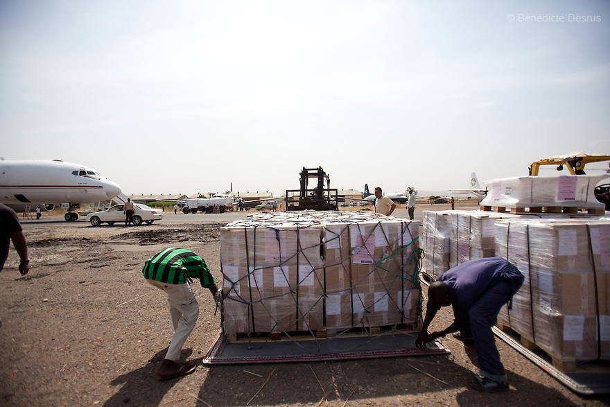 wednesday 22 december 2010 - Juba, South Sudan - Workers offload voting ballot forms printed in the UK for the South Sudan referendum, from an airplane at Juba airport. The plane carrying more than 7.3 million ballot forms and was surrounded by security forces and U.N. officials. The referendum on whether the oil-producing region should declare independence, scheduled for January 9,  2011 is the climax of a 2005 peace deal that ended decades of north-south conflict - Africa's longest civil war that was fought over ethnicity, religion, ideology and oil and that killed 2 million people. Photo credit: Benedicte Desrus