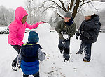 WINSTED, CT-011718JS03--Justin Fecto Sr., and Lily Hernandez of Winsted, right, help build a snowman with Lesslie Rodriguez, 12, of Torrington and Justin Fecto Jr., 2, at The Gilbert School in Winsted following Wednesday's snow fall. <br /> Jim Shannon Republican-American