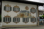Mural painted on wall of horses pulling cart and showing ornate artwork around the windows. Oberammergau, Bavaria, Germany.