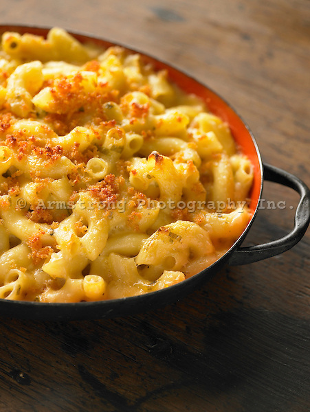 A serving dish of macaroni and cheese baked with browned bread crumbs on top.