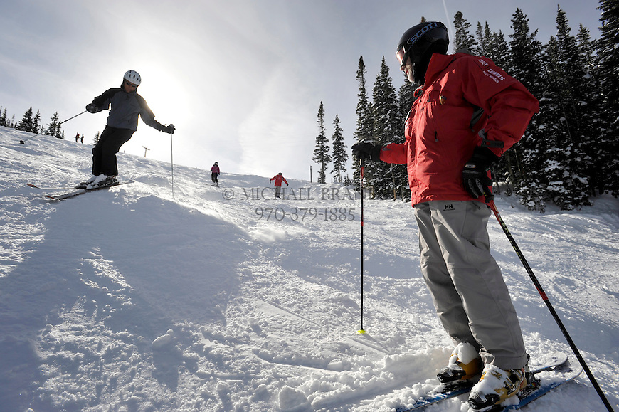 Instructor Alan Bush watches as Pete Louras, 57, of Aspen, makes a turn around a mogul on Aspen Mountain. Michael Brands for The New York Times.