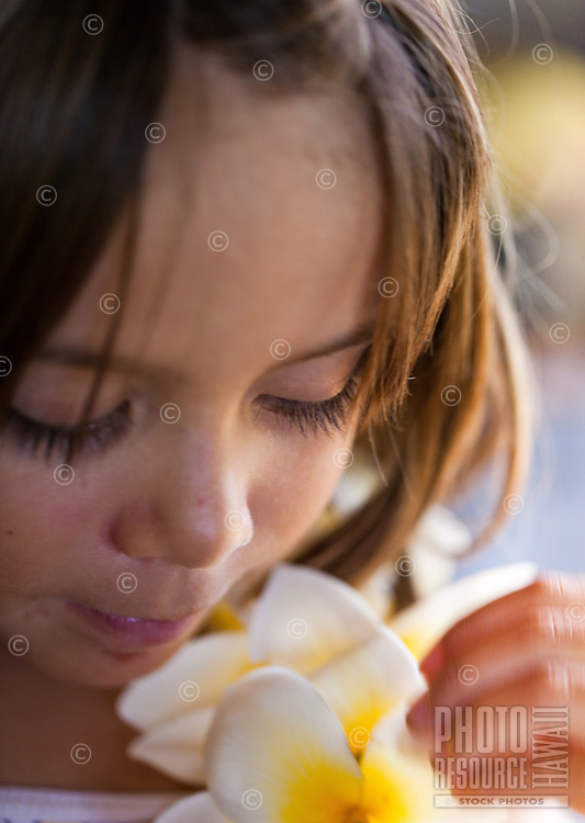 Young girl smelling a fragrant plumeria lei