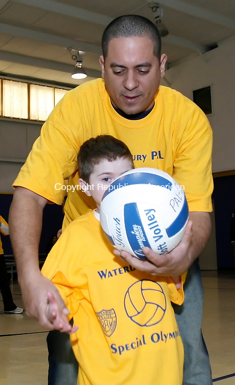 WATERBURY, CT, 01/20/09, 012009BZ01- Volunteer Edgar Hilario helps Sean Ladden, 8, serve a volleyball during an exhibition game at the Waterbury Police Activities League (PAL) building on Division Street in Waterbury Tuesday.  PAL announced a partnership with Special Olympics earlier in the day.<br /> Jamison C. Bazinet Republican-American