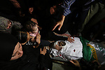 Relatives of Palestinian Abdul Karim Radwan, who was killed in an Israeli air strike, mourn over his body during his funeral in Rafah in the southern of Gaza Strip on July 20, 2018. Photo by Ashraf Amra