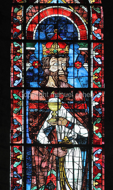 Melchizedek, King of Salem and priest, wearing a crown and swinging a censer, showing that he is a high priest. He holds a chalice containing bread, representing the bread he offered to Abraham after his victory over the enemy kings, lancet window from under the main North Rose stained glass window, 1233, on the Northern side of the transept of Chartres Cathedral, Eure-et-Loir, France. This window was offered by Blanche of Castile, then regent, mother of the future Saint Louis. Chartres cathedral was built 1194-1250 and is a fine example of Gothic architecture. Most of its windows date from 1205-40 although a few earlier 12th century examples are also intact. It was declared a UNESCO World Heritage Site in 1979. Picture by Manuel Cohen