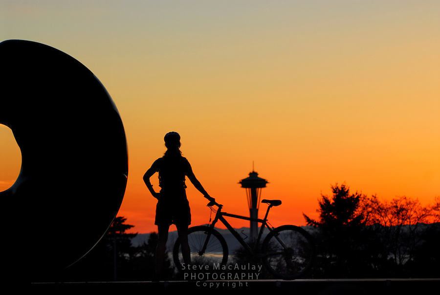 Female mountain biker checking out a colorful sunset and the Space Needle from Volunteer Park, Capitol Hill, Seattle, WA.